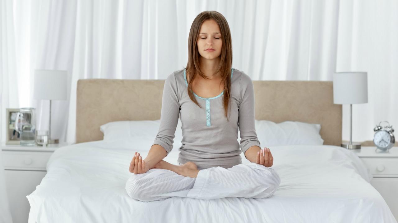 yatakta meditasyon yapan kadın
