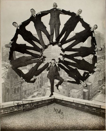 Man on Rooftop with Eleven Men in Formation on His Shoulders, c1930