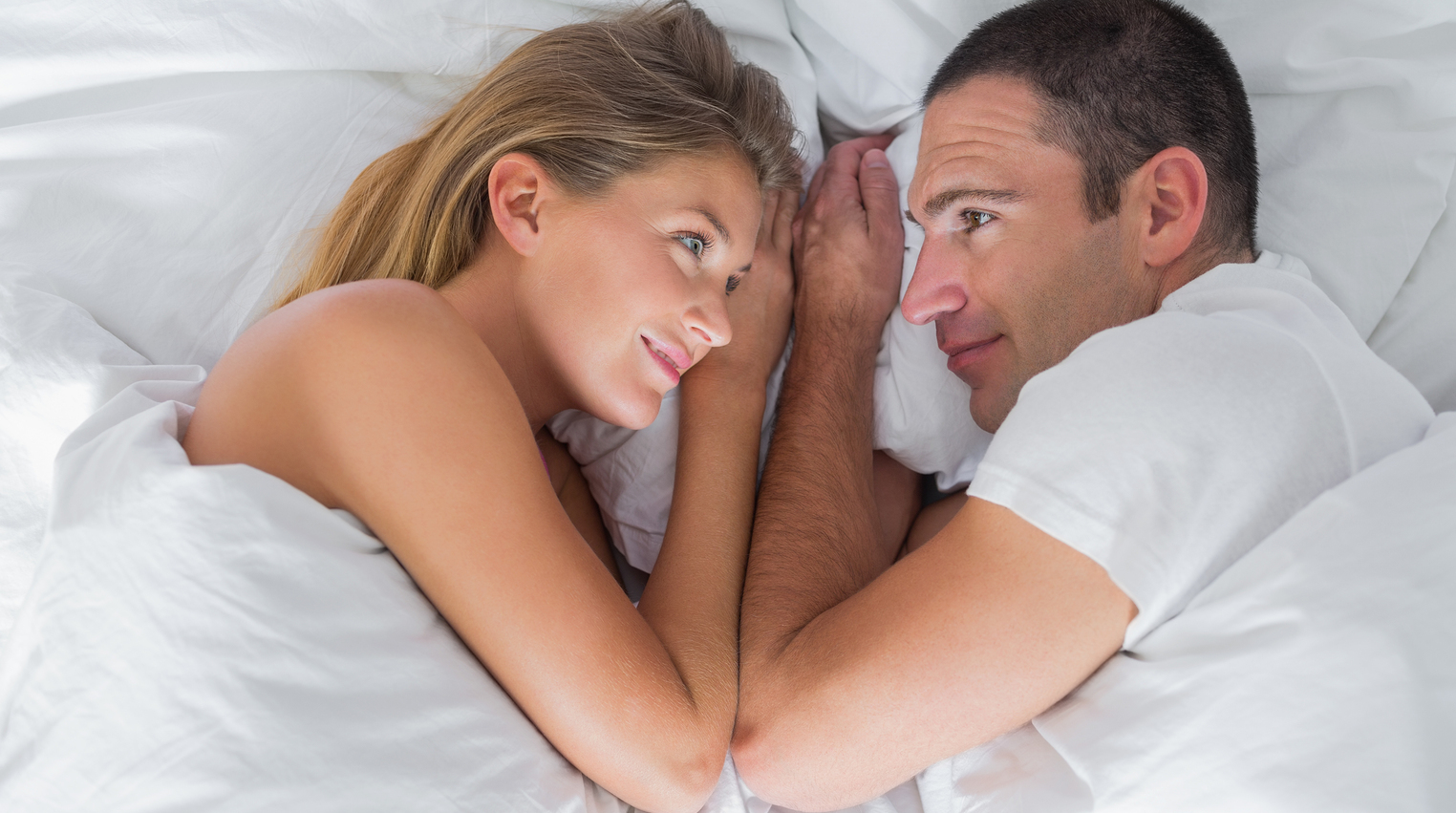 Cute couple lying and looking at each other in bed at home in bedroom