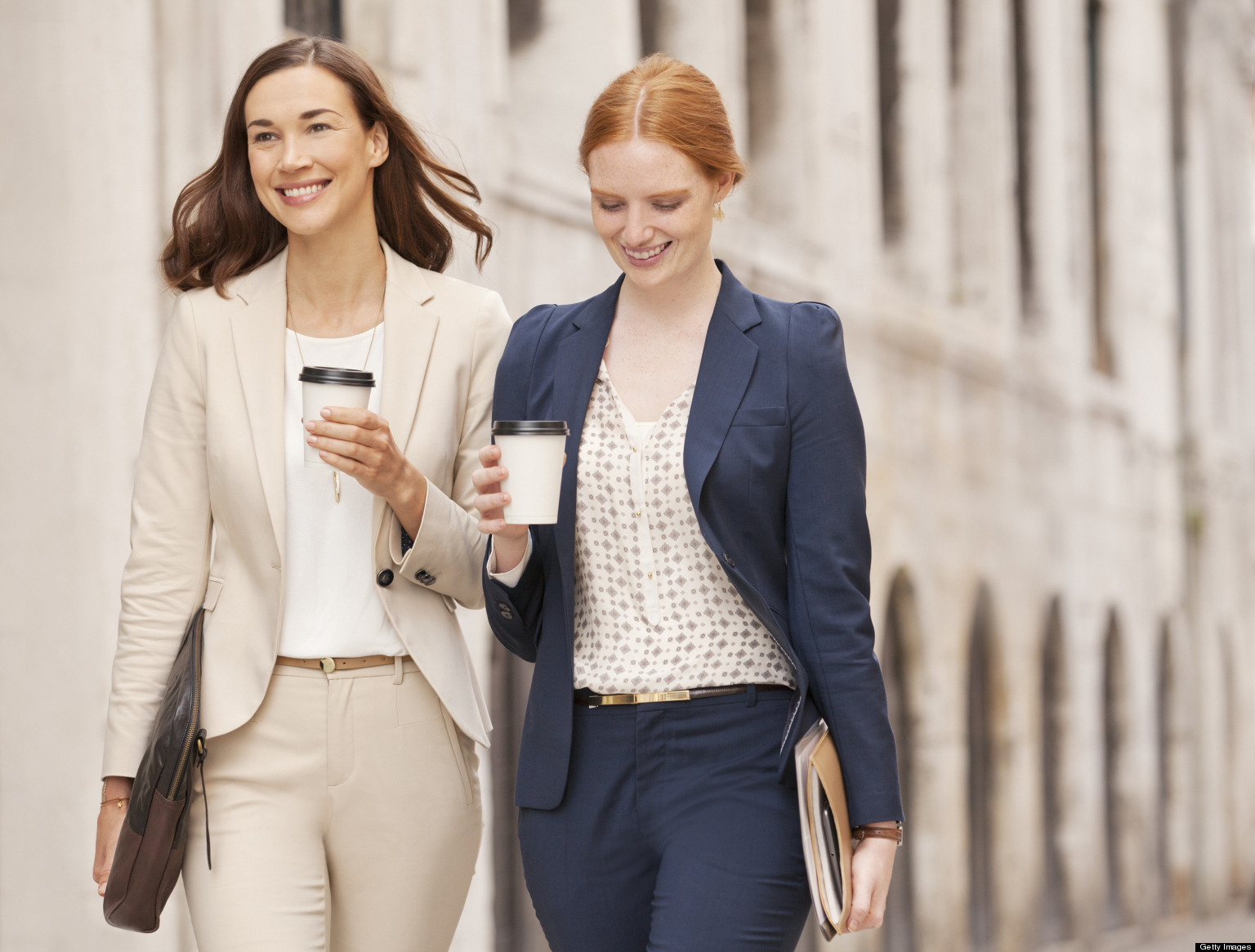Smiling businesswomen walking with coffee
