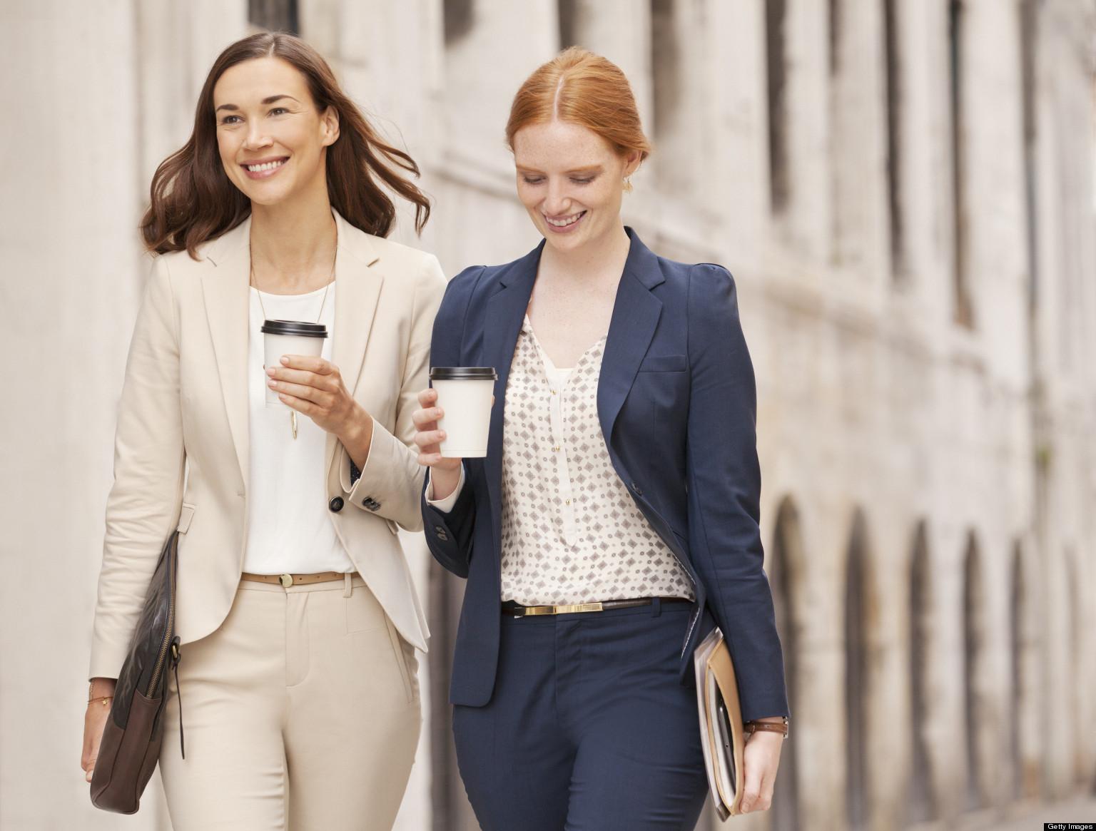 Smiling businesswomen walking with coffee